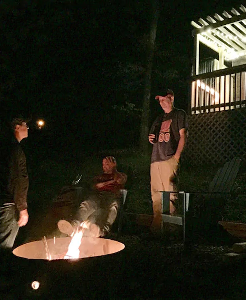 men sitting around a fire pit at night enjoying some drinks